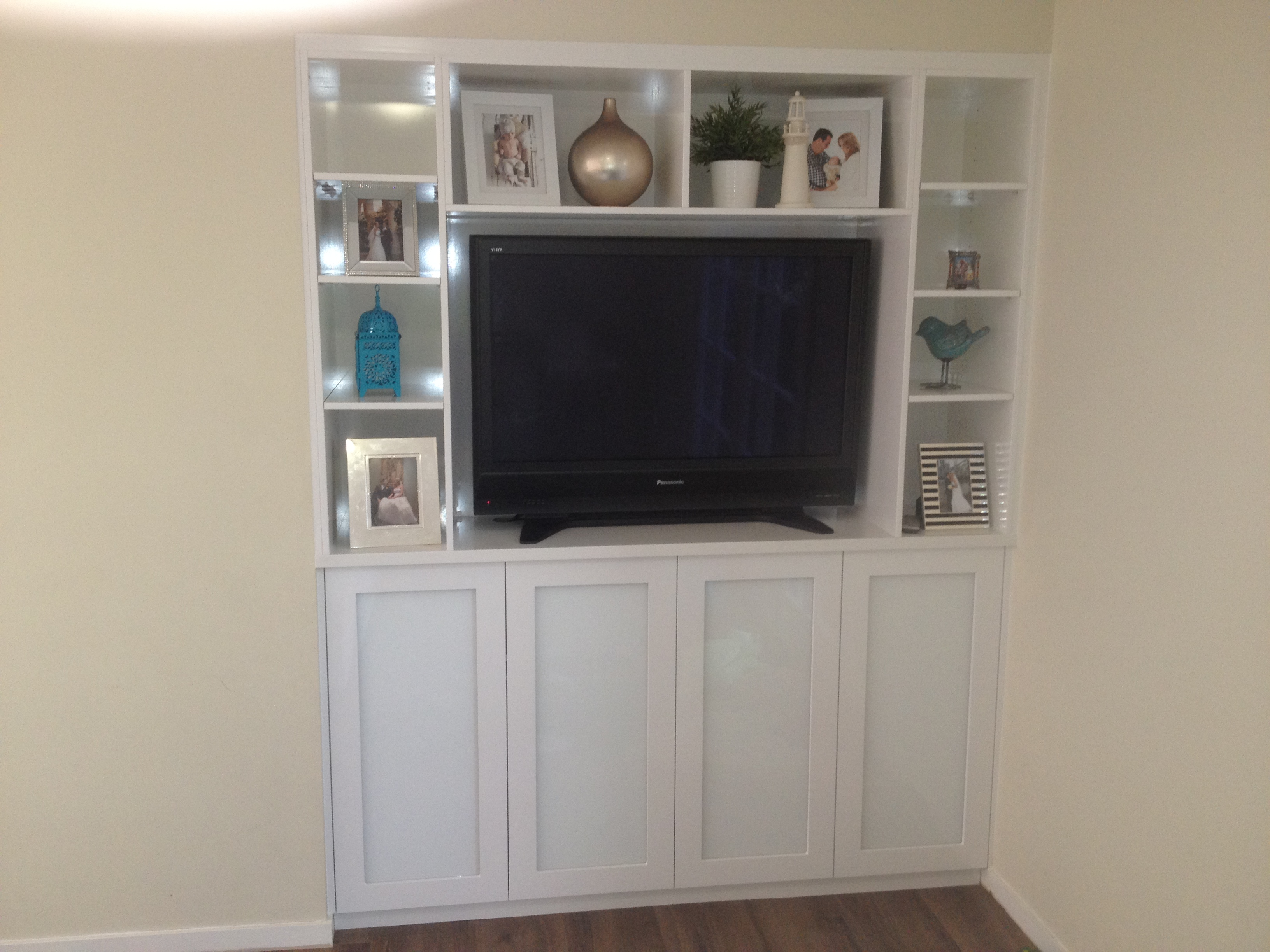 Custom Built In Display Unit With Lights And Glass Inserts In Doors